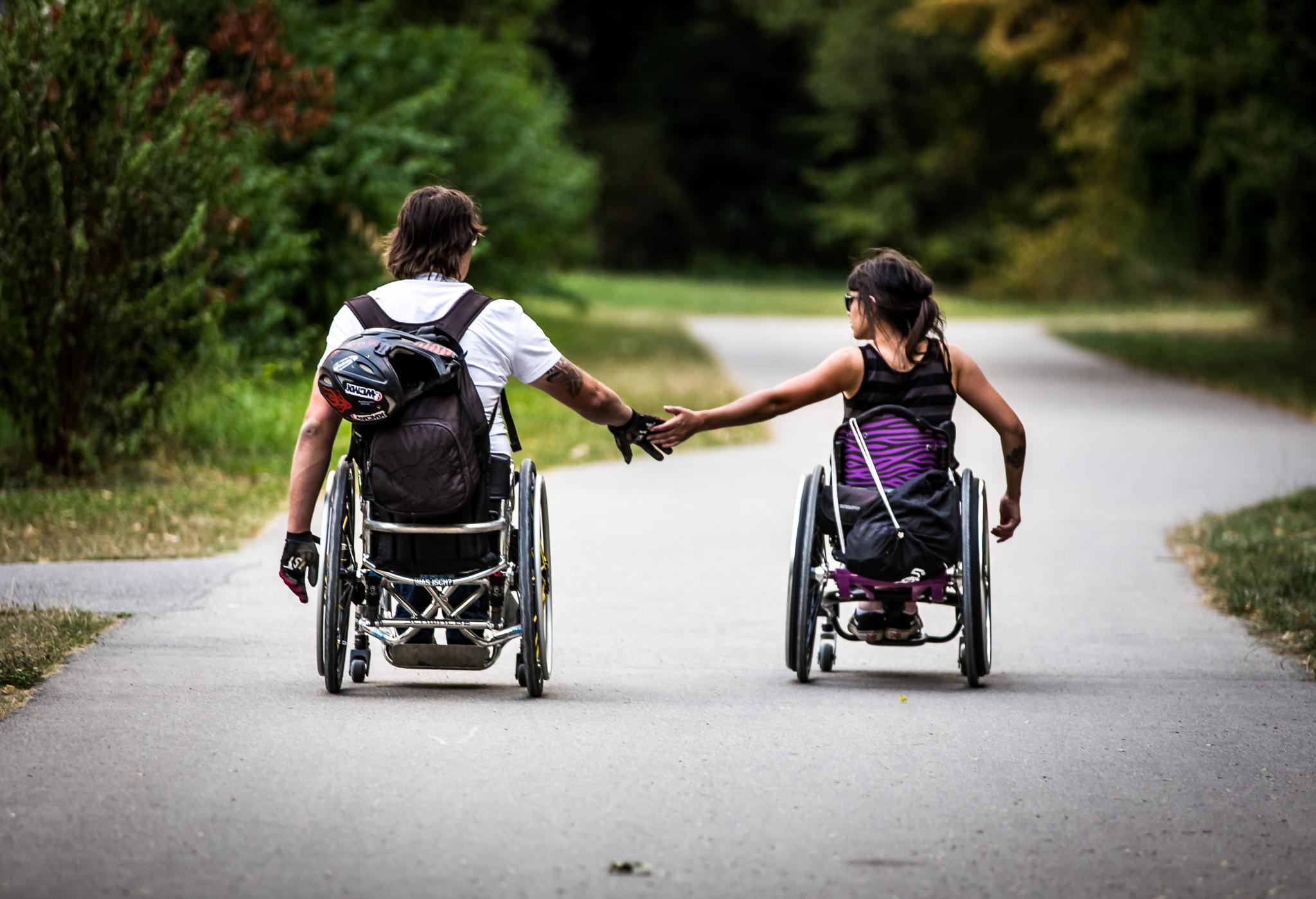 Zwei RollstuhlfahrerInnen halten Hand in einem Park
